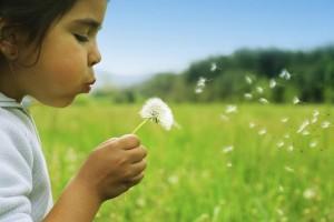girl-in-field-blowing-flower